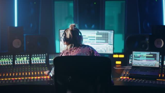 プロデューサー、オーディオエンジニアは、サウンドプルーフルームミュージシャン、アーティスト、パフォーマーが新しいアルバムから曲を歌う音楽レコードスタジオで新しいアルバムト� - クリエイティブな職業点の映像素材/bロール