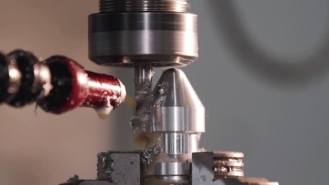 vídeos de stock, filmes e b-roll de produz detalhes metálicos na fábrica. máquinas-ferramentas para o metal funcionar. uma peça de trabalho metálica é usinada por uma máquina elétrica. cortando a tecnologia de processamento moderna de metal. refrigerante e lubrificação. - exatidão