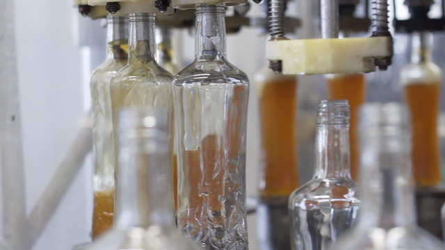 Production and bottling of alcoholic beverages. Spill of alcohol liquor in glass bottles at distillery. Glass bottles in conveyor belt in factory production line. Spillage of alcoholic beverages. video