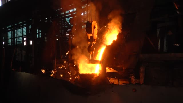 production department of casting in the flask. room for the manufacture of metal products by casting. casting shop for gasified models. the molten metal is poured from the induction furnace into the ladle. sparks of hot metal fly apart. - industria metallurgica video stock e b–roll