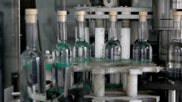 produzione di alcol in fabbrica. le bottiglie passano attraverso la catena di montaggio. - vodka video stock e b–roll
