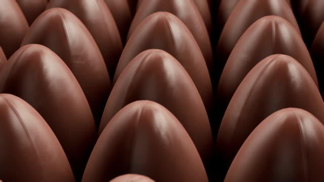 produzione di uova di pasqua nella fabbrica di cioccolato - easter video stock e b–roll