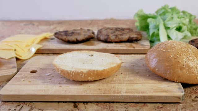 products for preparation of burgers: buns, cutlets, cheese, salad, on the table. side view. - formaggio spalmabile video stock e b–roll