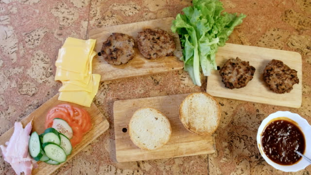 products for preparation of burgers: buns, tomatoes, cucumbers, cutlets, cheese, salad, sauce, bacon on the table. top view. - formaggio spalmabile video stock e b–roll
