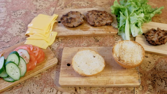 products for preparation of burgers: buns, tomatoes, cucumbers, cutlets, cheese, salad, sauce, bacon on the table. - formaggio spalmabile video stock e b–roll