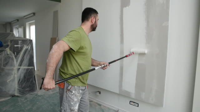 Profesional painter painting with paint roller Profesional painter painting with paint roller. Decorator at work painting a wall. house painter stock videos & royalty-free footage