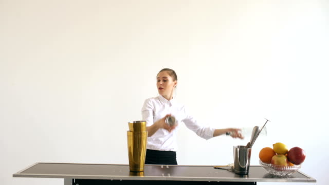 Professinal bartender girl juggling bottles and shaking cocktail at mobile bar table on white background video