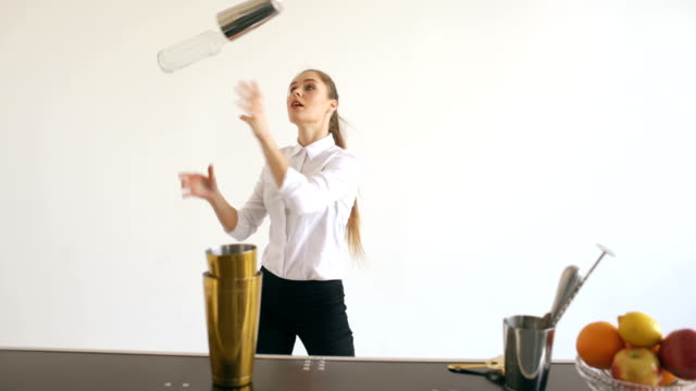Professinal bartender girl juggling bottles and shaking cocktail at mobile bar table on white background studio indoors video