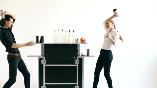 Professinal bartender man and woman juggling bottles and shaking cocktail at mobile bar table on white background - Vidéo