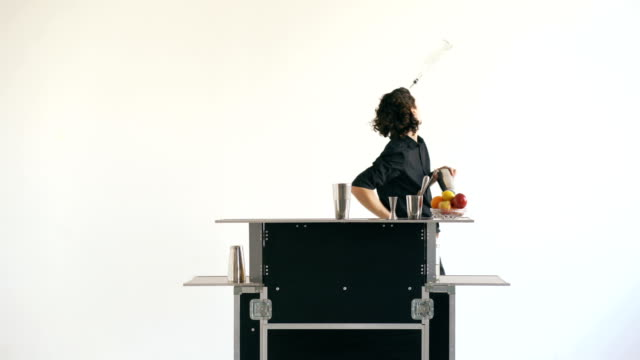 Professinal bartender man juggling bottles and shaking cocktail at mobile bar table on white background studio indoors video