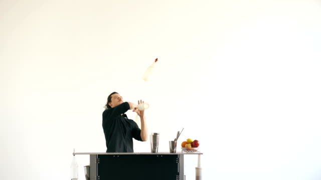 Professinal bartender man juggling bottles and shaking cocktail at mobile bar table on white background video