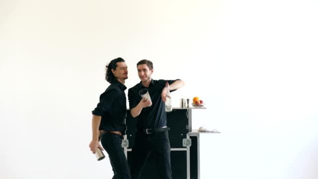 Professinal bartender men juggling bottles and shaking cocktail at mobile bar table on white background studio indoors video