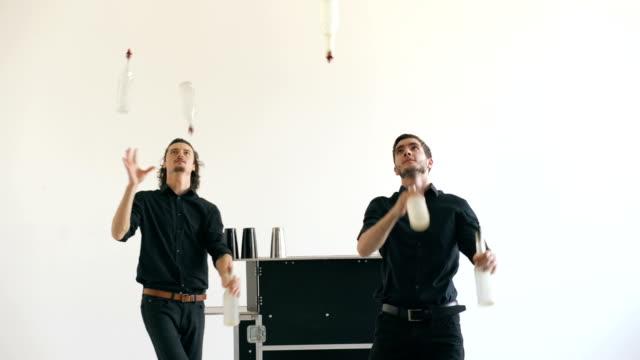 Professinal bartender men juggling bottles and shaking cocktail at mobile bar table on white background video