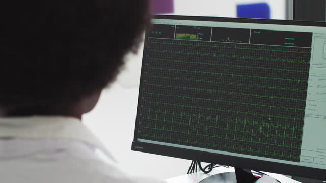 Professional African-American scientist is working on a vaccine in a modern scientific research laboratory. Genetic engineer workplace. Futuristic technology and science. Shooting from the back ECG