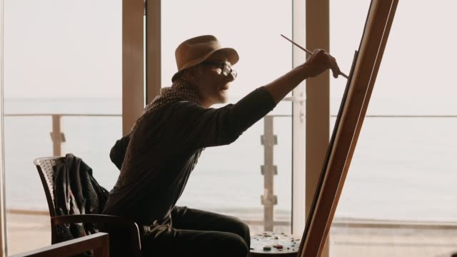 professional artist is engaged in drawing sitting on a chair by the sea - museo video stock e b–roll
