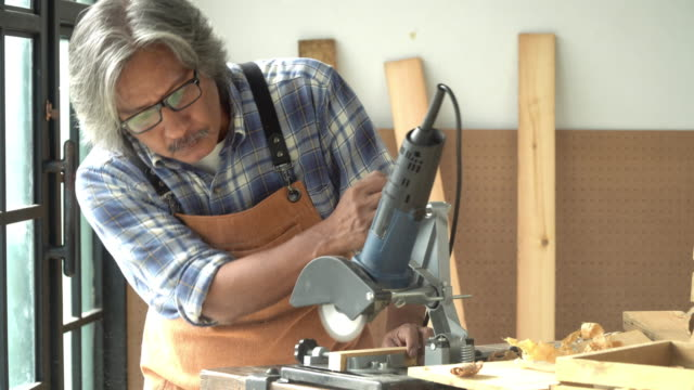 4K Professional Asian senior craftsman carpenter using carpentry chainsaw cutting plank of wood for production of modern wooden furniture in studio workshop. Retirement lifestyle DIY working concept.