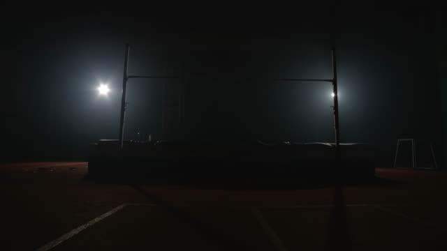 vidéos et rushes de un athlète professionnel effectue un saut par-dessus une barre transversale lors d'un saut en hauteur. et a renversé la barre - homme slip