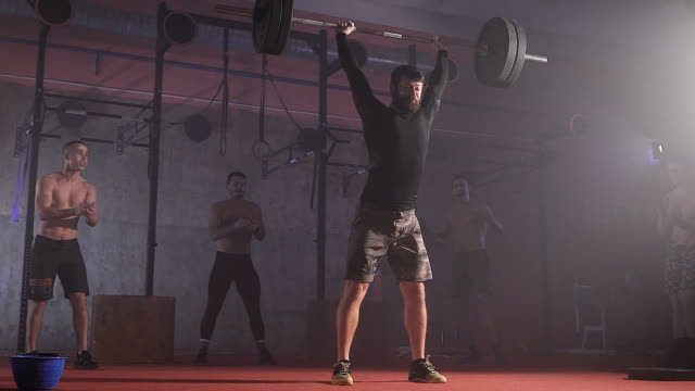 Professional athlete raises the bar with weight and holds it video