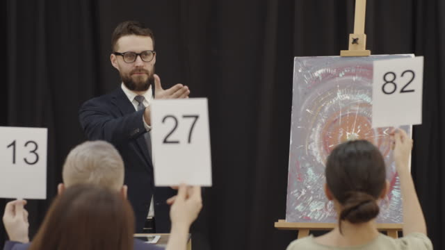professional auctioneer announcing bids at art auction - asta oggetto creato dall'uomo video stock e b–roll