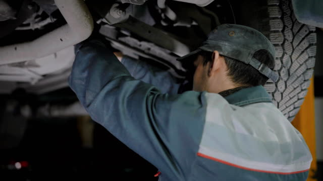 Professional automechanic is working on car troubles video