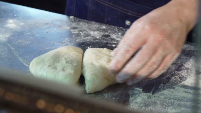 專業麵包師在廚房切面團 - 自製的 個影片檔及 b 捲影像