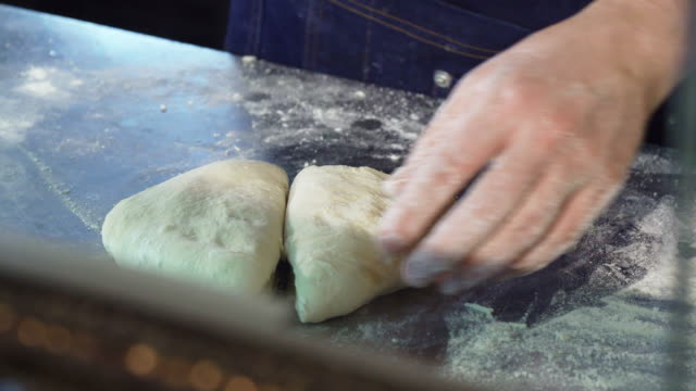 professional baker cutting dough at the kitchen - fatto in casa video stock e b–roll