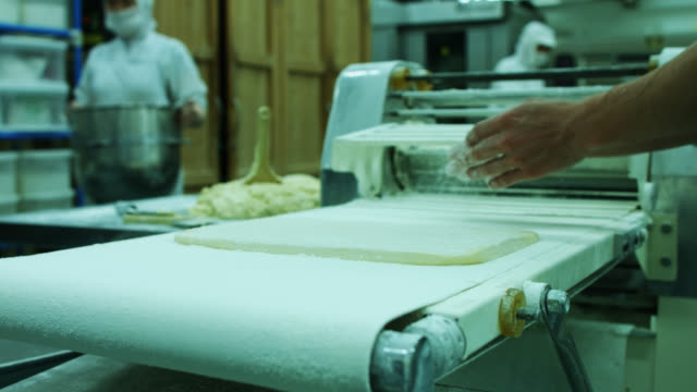 Professional Baker Rubbing Sheet of Dough