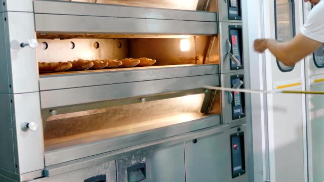 vidéos et rushes de boulanger professionnel, sortir le pain du four dans une cuisine commerciale - boulanger