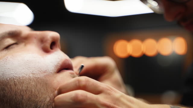 vídeos de stock e filmes b-roll de professional barber shaves customer beard with straight razor. beard cut with old-fashioned blade at barbershop. handsome macho man getting his beard shaved in studio. close-up shot - reto descrição física