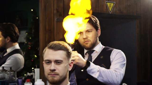vídeos de stock, filmes e b-roll de barbeiro profissional trabalhando tratamento de cabelo de fogo ardente em seu cliente - estilo de cabelo