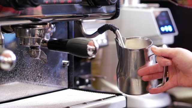 Professional barista frothes milk in stainless frothing jug for cappuccino to perfect temperature Professional barista frothes milk in stainless frothing jug for cappuccino to perfect temperature stainless steel stock videos & royalty-free footage