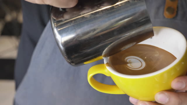 Professional Barista making pouring stream milk latte art pattern in cup.