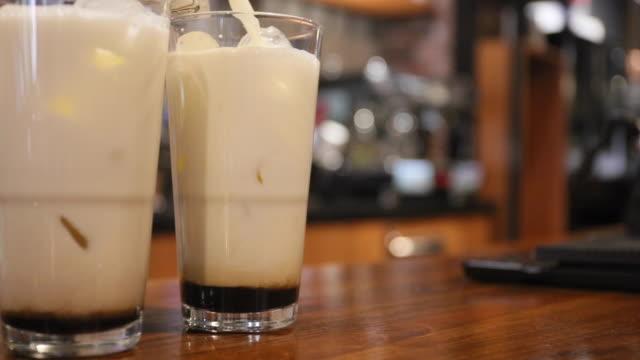 vídeos de stock e filmes b-roll de professional barista pouring coffee into a glass with ice and adding milk in a busy coffee shop - bebida fresca