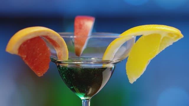 Professioneller Barmann schmückt einen grünen Cocktail mit Zitrusfrüchten. Bartender bereitet Cocktails auf defokussiertem Hintergrund zu und gießt und serviert einen Cocktail. Barman bereitet bunten Cocktail. Zeitlupe. – Video