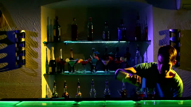 Professional barman making cool, amazing tricks using bottle, juggling standing behind the bar, catching, throwing up, and pouring two liquids, slow motion video