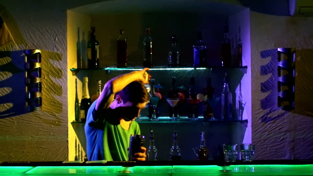 Professional barman making cool, amazing tricks using shaker and bottle, juggling standing behind the bar, catching, throwing up, imitation, slow motion video