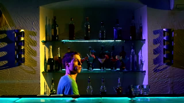 Professional barman making cool, amazing tricks using three shakers, juggling standing behind the bar, catching, throwing up, slow motion video