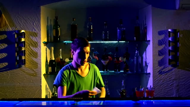Professional barman using bottle standing behind the bar, serving and mixing cocktail, slow motion video