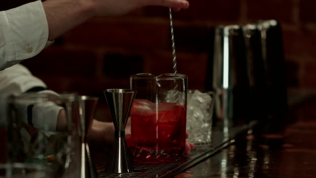 Professional bartender at work in bar mixing ice and liquor in glass for drink video