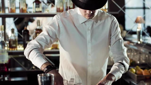 黒い帽子でプロのバーテンダーは、バーでカクテルを作る - バーテンダー点の映像素材/bロール
