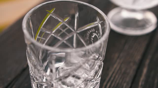 Professional bartender throws ice into empty glass shot