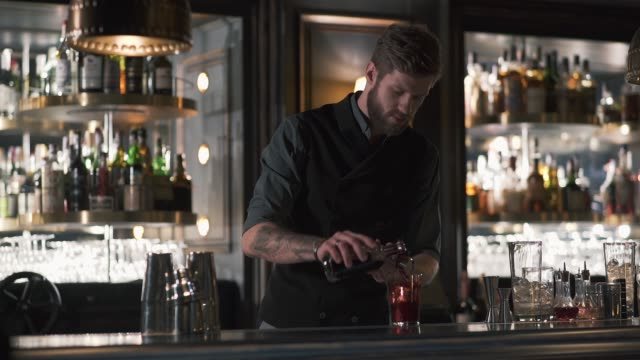Professional bearded bartender pouring rum in the metal beaker, then in glass. video