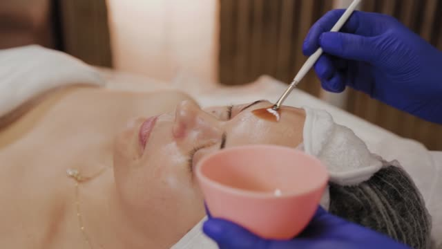 Professional beautician applies face serum with a brush Professional beautician applies face serum with a brush serum sample stock videos & royalty-free footage