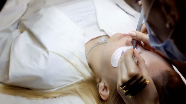 Professional beautician makes eyelash extension to client in beauty shop video