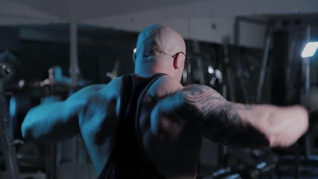 professioneller bodybuilder tun hantelheben zur seite in einem sportverein - menschliches gelenk stock-videos und b-roll-filmmaterial