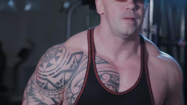 vídeos de stock, filmes e b-roll de fisiculturista profissional treina bíceps com halteres em clube esportivo - braço humano