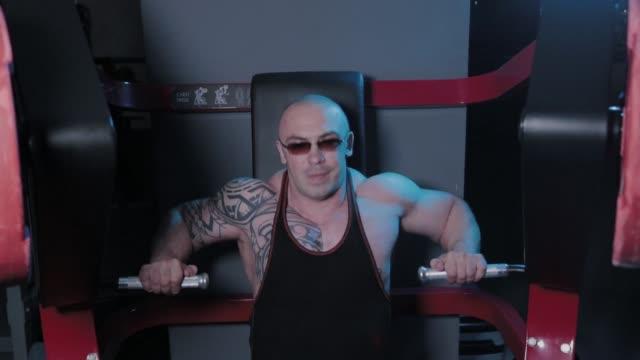 vidéos et rushes de le bodybuilder professionnel entraîne des muscles pectoraux sur le simulateur dans un club de sport - bras humain