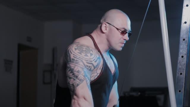 vidéos et rushes de le bodybuilder professionnel entraîne des triceps sur un simulateur de bloc dans un club de sport - bras humain