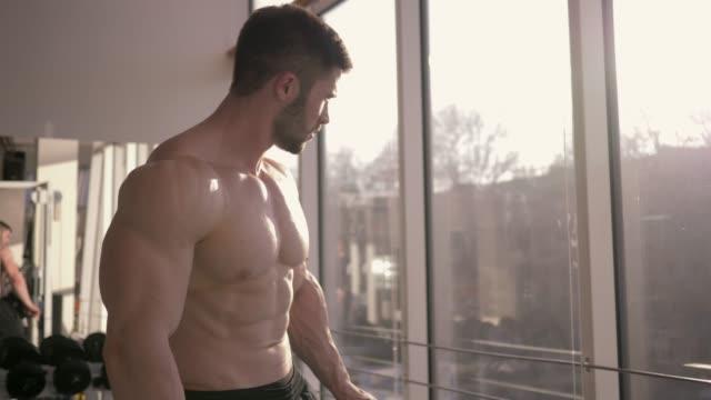 전문 보디 빌딩, 스포츠 남성 긴장에 근육을 유지 하 고 햇빛에 스포츠 센터에서 강도 훈련의 결과에서 보이는 - 보디 빌딩 스톡 비디오 및 b-롤 화면