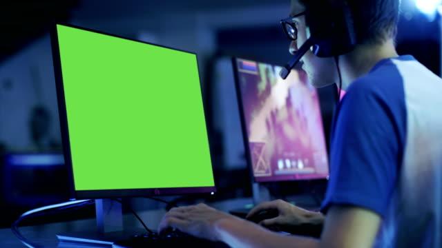 プロ男の子緑色の画面表示のビデオ ゲームでゲーマーの演劇。彼は、e スポーツ大会/インター ネット カフェで演じています。彼は身に着けているヘッドセットとマイクに向かってコマンドを話します。 - ゲーム ヘッドフォン点の映像素材/bロール